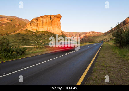 A car speeds by Brandwag Buttress monument in Golden Gate Highlands National Park, South Africa. - Stock Photo