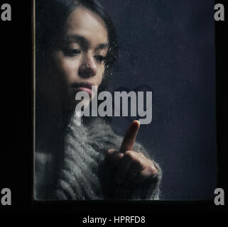 Portrait of woman drawing heart on wet window - Stock Photo
