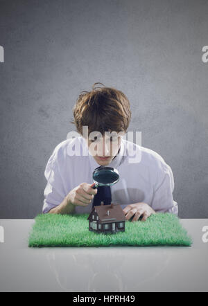Young man holds a magnifying glass over a miniature house. - Stock Photo