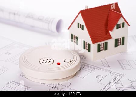 Smoke detector with house and blueprints   usage worldwide - Stock Photo