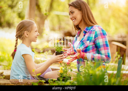 Cute smiling little girl assisting her mother planting flowers in a backyard. - Stock Photo