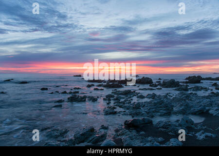 Kaikoura, Canterbury, New Zealand. View across the Pacific Ocean from rocky shoreline at dawn, pink sky reflected - Stock Photo