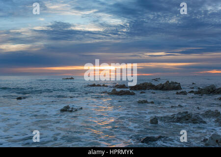 Kaikoura, Canterbury, New Zealand. View across the Pacific Ocean from rocky shoreline at sunrise, golden light reflected - Stock Photo