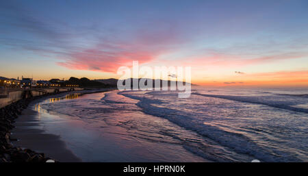 Dunedin, Otago, New Zealand. View over the Pacific Ocean off St Clair Beach at dawn, pink sky reflected in water. - Stock Photo