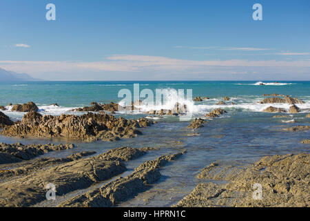 Kaikoura, Canterbury, New Zealand. View from rocky shore across the turquoise waters of the Pacific Ocean. - Stock Photo