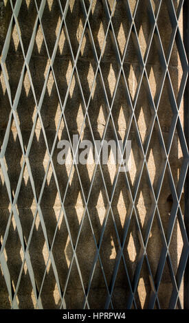 Sunlight and shadows from expanded metal grille, Macau - Stock Photo