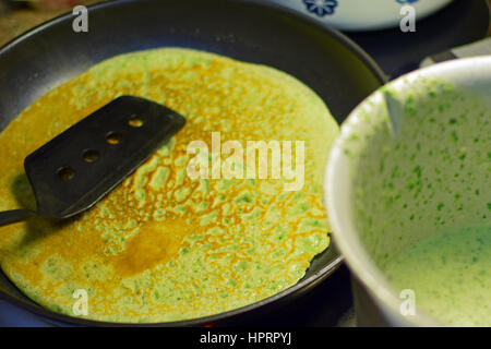 Making spinach pancakes close up. One ready on frying pan and more batter in bowl. - Stock Photo