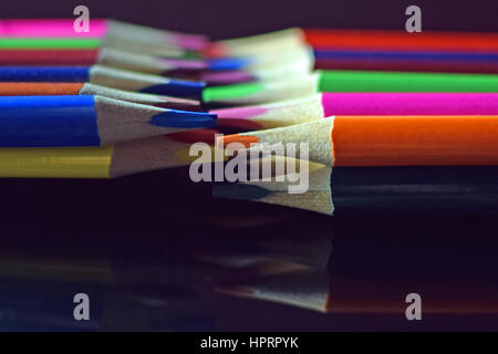 Close up of colored pencils on black reflective surface. - Stock Photo