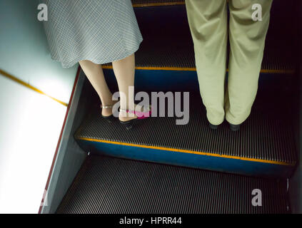 Legs of man and woman standing on up escalator on Pyongyang metro,  DPRK / North Korea - Stock Photo