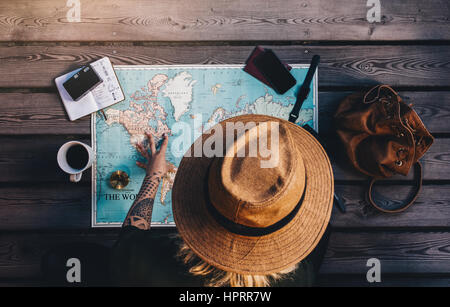 Tourist exploring the world map sitting on wooden floor with compass and other travel accessories. Young woman wearing - Stock Photo