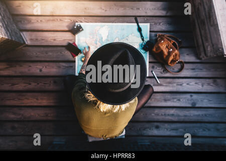Top view of woman wearing hat looking at the world map. Tourist sitting on wooden floor exploring the world map. - Stock Photo