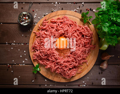 Homemade raw minced meat with egg and herbs closeup, top view - Stock Photo