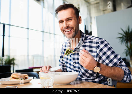 Handsome bearded man in checked shirt holding fork eating in cafe and smiling looking at camera - Stock Photo