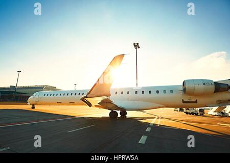 Daily life at the international airport. The airplane is taxiing to the runway during sunset. - Stock Photo