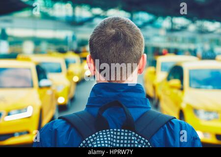 Handsome traveler is waiting for taxi at the airport. - Stock Photo
