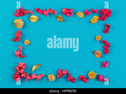 Pink and yellow dried flower plants rectangular border frame on blue background. Top view, flat lay. Copy space - Stock Photo