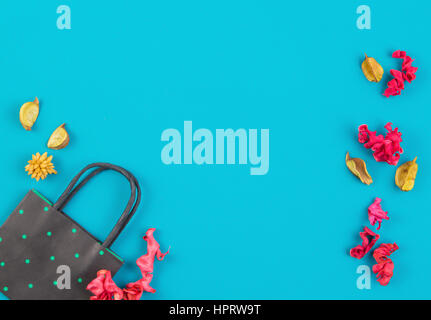 Black and green polka dot paper shopping bag and colorful dried flowers plants on blue background. Top view, flat - Stock Photo