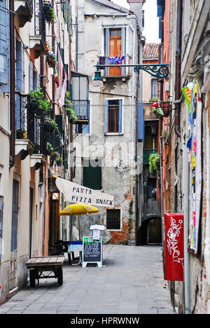 Restaurant down a narrow back street in Venice, Italy - Stock Photo