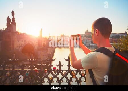 Traveler with backpack taking photo by mobile phone. Young tourist near Charles bridge at the sunset. Prague, Czech - Stock Photo