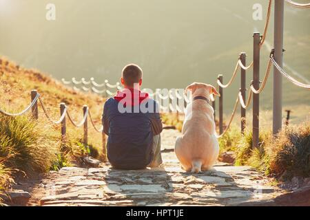 Man with dog on the trip in the mountains. Young tourist and his dog are resting and together watching the sunset. - Stock Photo
