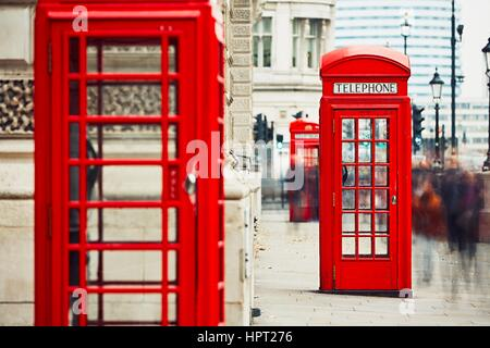 Crowd of people and red telephone boxes on the street in London, The United Kingdom of Great Britain and Northern - Stock Photo