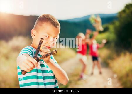 Little boy holding slingshot with stone. Boy is playing with his sisters in rural landscape. - Stock Photo