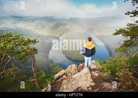 Traveler on the top of rock. Young man enjoying view on river valley in morning fog. Vltava river in Central Bohemia, - Stock Photo