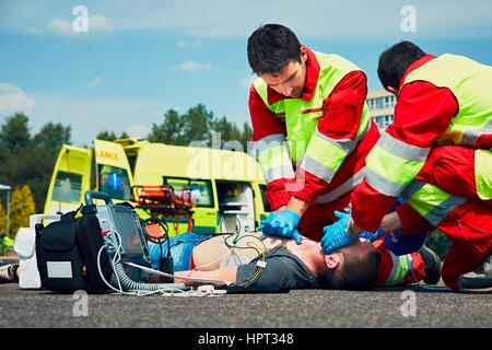 Cardiopulmonary resuscitation. Rescue team (doctor and a paramedic) resuscitating the man on the street. - Stock Photo