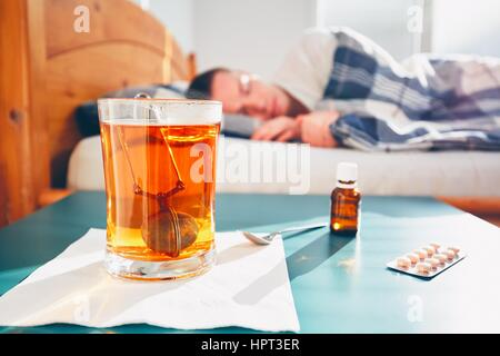 Sick man is lying in bed under blanket. Selective focus on the hot tea and medicine on the table. - Stock Photo