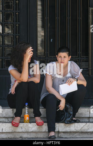 Bucharest, Romania, July 22, 2009: Two students are smoking on the stairs of a university in Bucharest. - Stock Photo