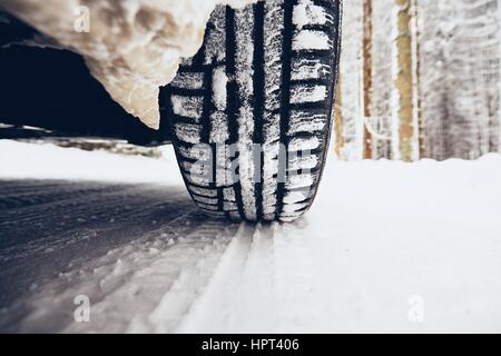 Detail of the tire on winter road. - Stock Photo