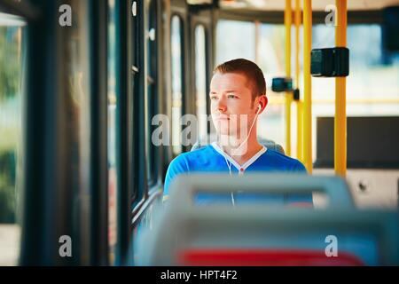 Loneliness man is wearing headphones and listening to music. Everyday life and commuting to work by public transportation. - Stock Photo