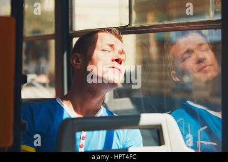 Everyday life and commuting to work by public transportation. Handsome young man is traveling by tram (bus). Tired - Stock Photo