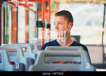 Sad young man is traveling by tram (bus). Everyday life and commuting to work by public transportation. Man is wearing - Stock Photo