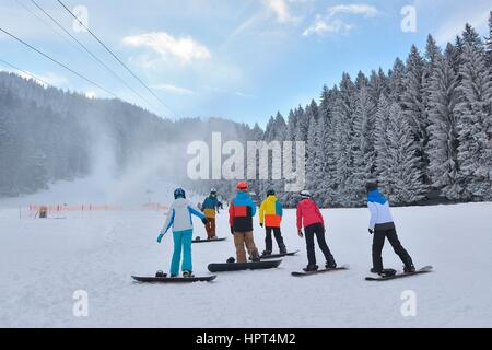Group of snowboarders resting on the snow while listening to the instructor - Stock Photo