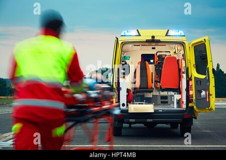 Emergency medical service. Paramedic is pulling stretcher with patient to the ambulance car. - Stock Photo