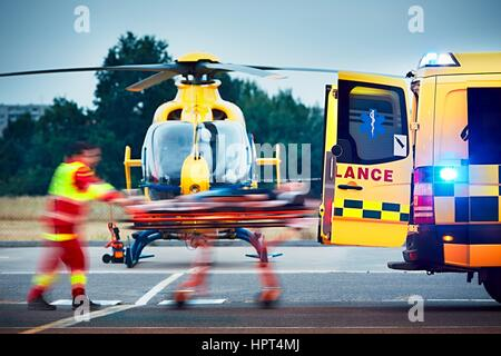 Cooperation between air rescue service and emergency medical service on the ground. Paramedic is pulling stretcher - Stock Photo