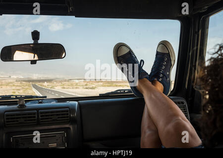 Woman sitting in car with feet up on dashboard - Stock Photo