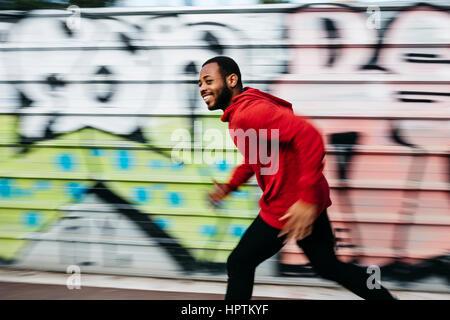 Smiling young man wearing red hoodie running along a graffiti wall - Stock Photo