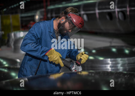 Factory worker operating steel cutter - Stock Photo