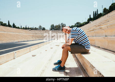 Greece, Athens, man sitting in the stands of the Panathenaic Stadium - Stock Photo