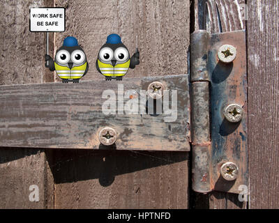 Comical bird construction workers perched on an old rusty hinge with health and safety message work safe be safe - Stock Photo