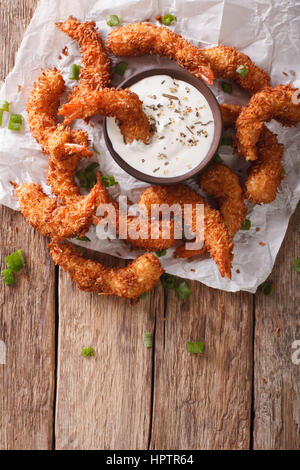 prawns fried in coconut close-up and cream sauce on the parchment on the table. vertical view from above - Stock Photo