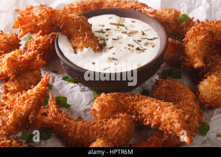 prawns fried in coconut close-up and cream sauce on the parchment on the table. horizontal - Stock Photo