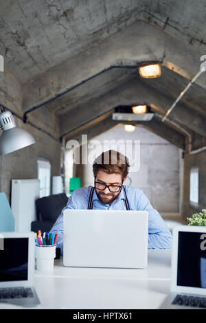 Designer working on laptop at creative agency office - Stock Photo