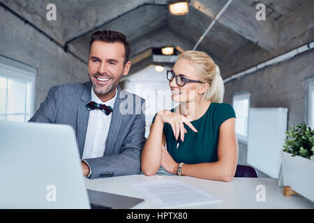 Two business people working on laptop at modern office - Stock Photo