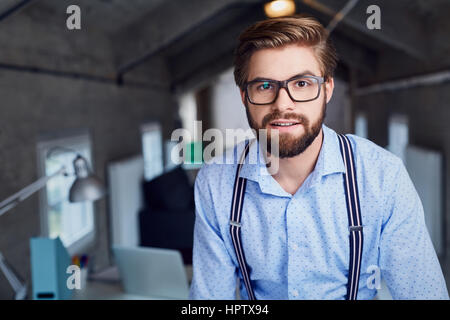Portrait of handsome designer wearing glasses in office - Stock Photo