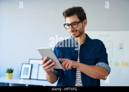 Happy web designer using digital tablet working from home office - Stock Photo