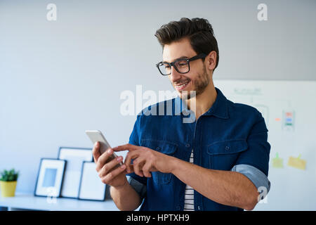 Happy web designer, freelancer using smartphone, working from home office - Stock Photo