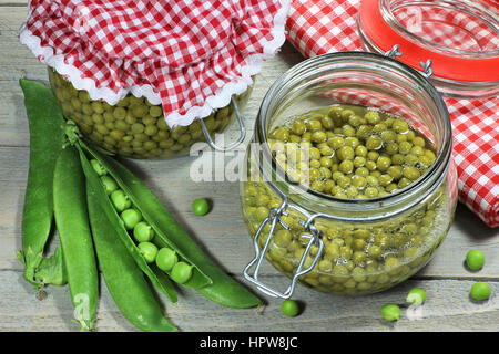 home canned peas on wooden table - Stock Photo